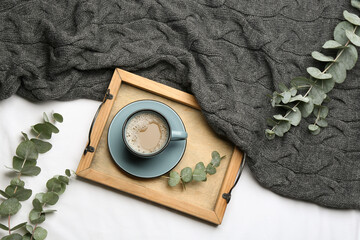 Flat lay composition with coffee and warm plaid on white bedsheet