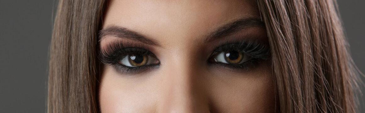 Close up of woman eyes with smokey eyes makeup and fake lashes, studio shot, looking to camera.