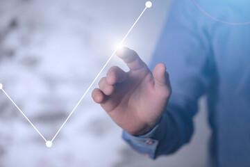 Obraz Dłoń dotykająca rosnący wykres. Koncepcja zysku, odbudowy rynku i kapitałów - fototapety do salonu