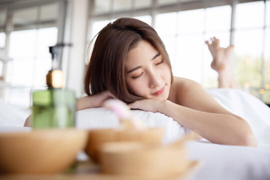 Woman Lying Down on Massage Bed withing for Spa Treatment