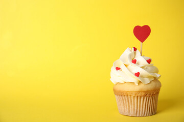 Tasty cupcake on yellow background, space for text. Valentine's Day celebration