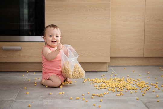 Happy baby making mess with bag of cereal