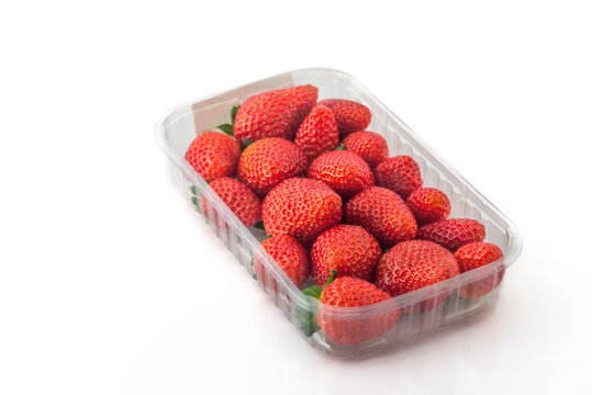 red ripe strawberry in plastic box of packaging for sale  on white background