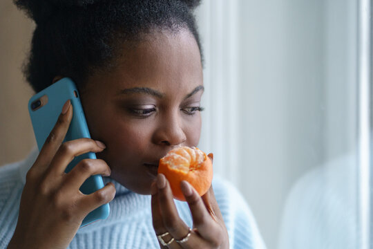 Sick afro woman trying to sense smell of half fresh tangerine orange, talking on phone, has symptoms of Covid-19, corona virus infection - loss of smell and taste. One of the main signs of the disease
