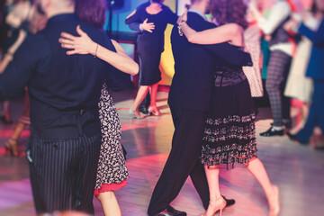 Couples dancing traditional latin argentinian dance milonga in the ballroom, tango salsa bachata kizomba lesson in the red lights, dance festival