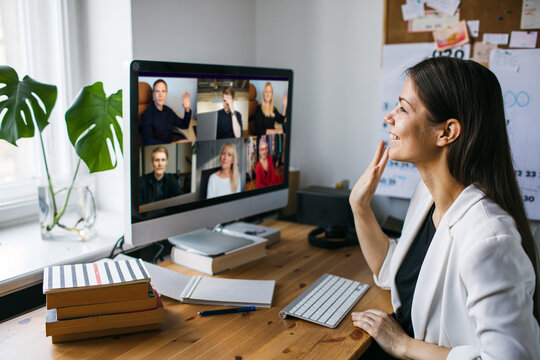 Young woman having Zoom video call via a computer in the home office. Stay at home and work from home concept during Coronavirus pandemic.