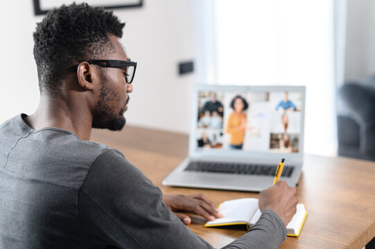 An African-American male student watching online webinars, video classes, educational training on a laptop and taking notes. A back view multiracial millennial has video call, virtual meeting