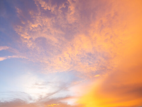 photography of sunset sky, abstract golden yellow sky, sunrise morning over clouds. skies covered colorful light rays shine through clouds. sunbeam flare spreading on beautiful nature dawnlight.