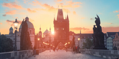Charles Bridge at dawn: silhouettes of Old Bridge Tower, churches and spires of Old Prague on a sunrise, panoramic image.