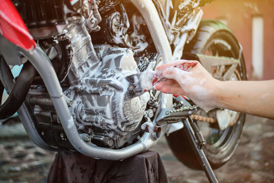 Close-up Of Hand Cleaning Motorcycle With Paintbrush