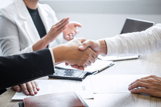 Business People Shaking Hands With Colleague Clapping In Background