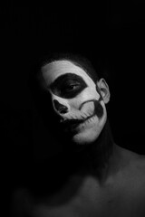 Portrait Of Man With Face Paint Against Black Background