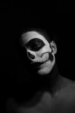 Portrait Of Man With Face Paint Against Black Background
