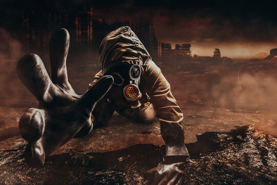 Photo of a dying stalker in jacket and gloves in damaged gas mask with filter reaching out his hand to camera on destructed apocalyptic wasteland city background.