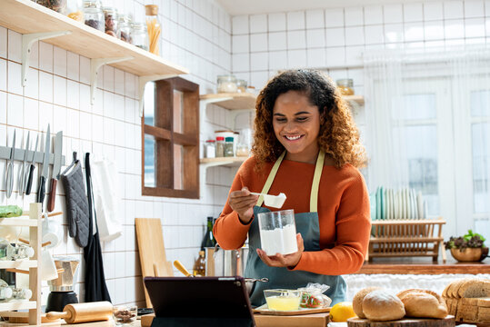 Young Afican American woman learning online  cooking class via tablet computer in kitchen at home