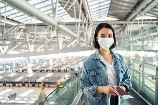 Portrait of female passenger wearing face mask standing in the airport