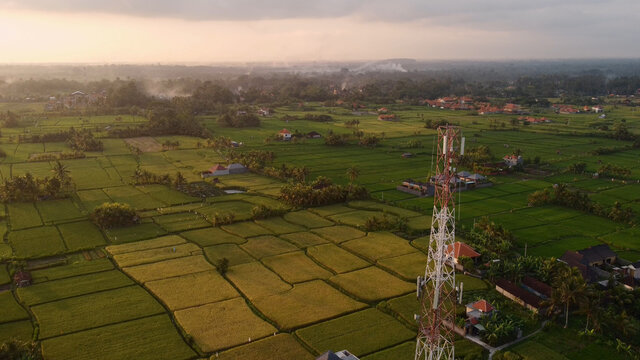 5g telecom tower antenna at sunset in the rice field green land natural landscape data smartphone wireless fast internet connection in remote area