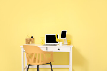 Stylish workplace with modern gadgets against color wall in room