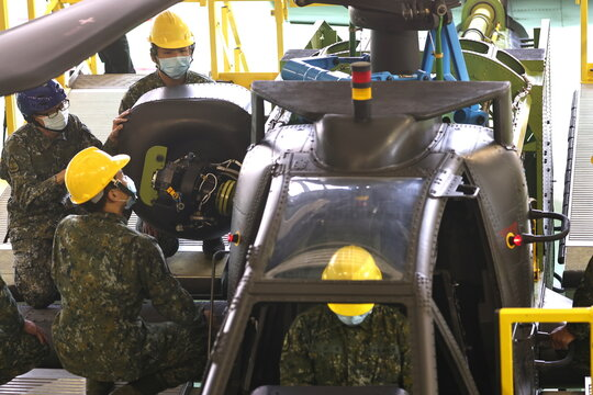 Air Force officers demonstrate maintenance work on an AH-64 Apache attack helicopter at a military base in Tainan,