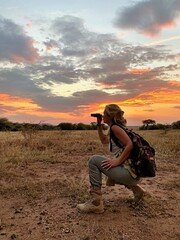 Side View Of Woman Looking Through Binoculars On Field Against Sky During Sunset