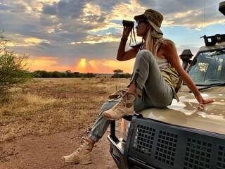 Obraz Woman On Vehicle Field Against Sky During Sunset - fototapety do salonu