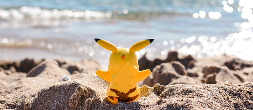 Pikachu figure model sitting on a sandy beach by the sea. Banner.