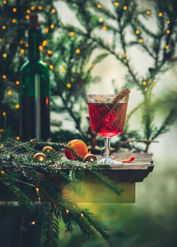 Glass of mulled wine with pine branches and fairy lights on background