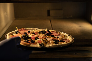 Italian pizza on a scoop is placed in a traditional illuminated electric oven during production. Wall mural