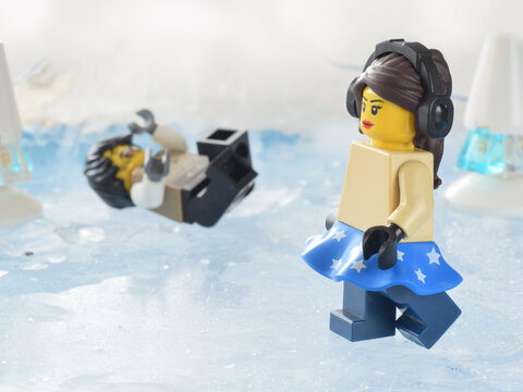 Plastic minifigure lego are on ice. Editorial illustrative image to people in winter on snow. Danger or falling.