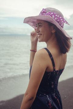"Beach photoshoot with a beautiful laughing girl on the beach ""Pantai bias lantang, Bali"" with fashion hat."