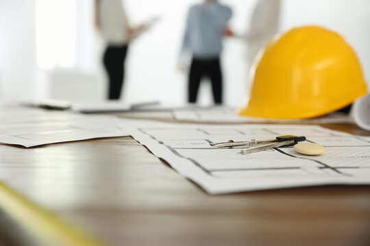 Colleagues in office, focus on table with construction drawings and tools