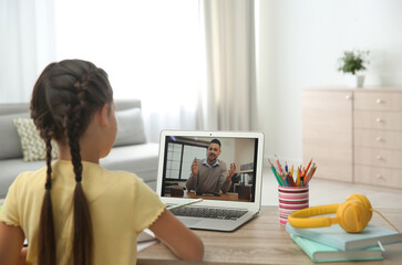 Distance learning, studying at home. Girl having online school lesson with teacher during...