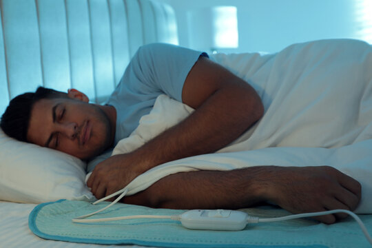 Man sleeping on electric heating pad in bed at night