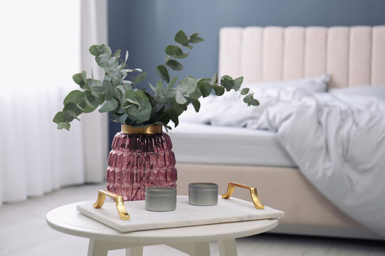 Candles and eucalyptus branches on white table in bedroom. Interior element
