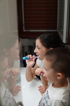 High Angle View Of Siblings Brushing Teeth In Bathroom