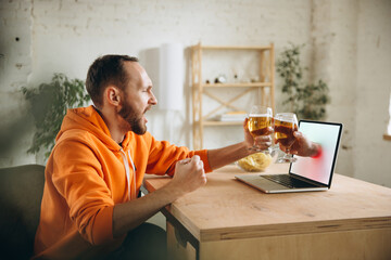 Clinking. Young man drinking beer during meeting friends on virtual video call. Distance online...