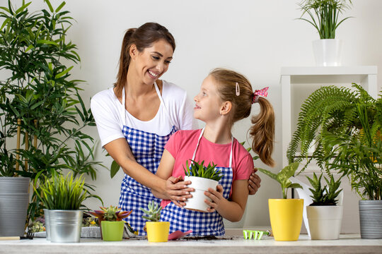 Family of plant lovers practicing their planting skills, two ladies, a woman and girl, holding a flowerpot