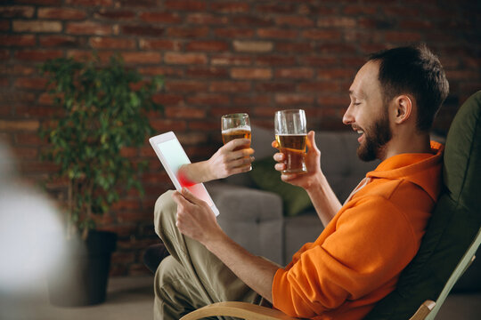 Happiness. Young man drinking beer during meeting friends on virtual video call. Distance online meeting, chat together on tablet at home. Concept of remote safe meetings and entertainment.