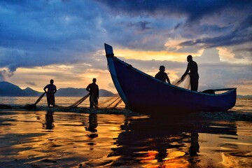 Obraz Silhouette People Fishing In Sea Against Sky During Sunset - fototapety do salonu