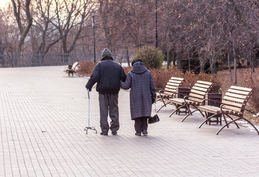 Grandpa leans on a cane while walking with grandmother