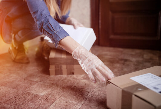 Delivery services courier during the Coronavirus (COVID-19) pandemic, close-up of cardboard box holding by a courier wearing  protective face mask and latex gloves at home front door online shopping