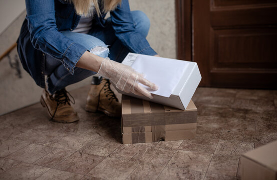 Delivery services courier during the Coronavirus (COVID-19) pandemic, close-up of cardboard box holding by a courier wearing  protective face mask and latex gloves at home front door
