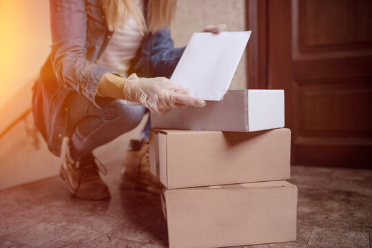 Delivery services courier during the Coronavirus (COVID-19) pandemic, close-up of cardboard box holding by a courier wearing  protective face mask and latex gloves at home front door at home