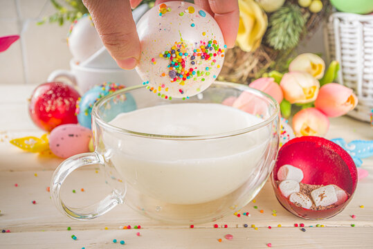 Festive Easter hot chocolate bomb. White chocolate bomb for hot cocoa drink, with marshmallow and sugar sprinkles