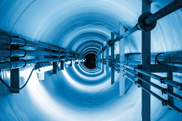Fototapeta Confined space inside underground tunnel. Construction from engineering technology for infrastructure i.e. power line or cable, steel pipe in perspective view. To transport water, gas and electricity.