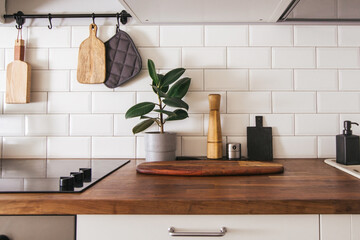 Obraz Kitchen brass utensils, chef accessories. Hanging kitchen with white tiles wall and wood tabletop.Green plant on kitchen background - fototapety do salonu