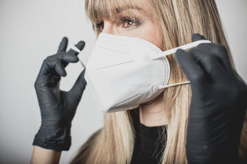 young, blond beautiful woman puts ffp2 protective mask on with protective medical gloves for...