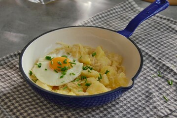 Wall Mural - Mashed potatoes with sauerkraut, fried egg and chives in pan