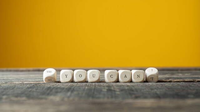 Wooden dices turning to spell a Yes you can sign