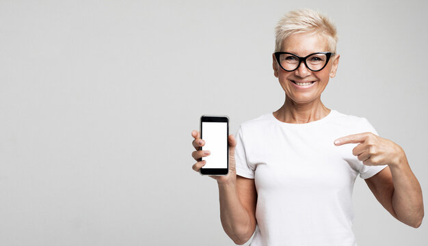 Modern lifestyle, old people and electronic gadgets concept. Attractive elderly female with pixie blonde hair presents new smartphone over light grey background.